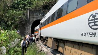 People walk next to a train which derailed in a tunnel north of Hualien