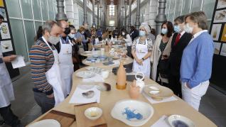 Representantes de los artesanos, de los cocineros y del Gobierno autónomo observan las colecciones de vajillas.
