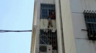 Angustioso rescate de los bomberos a un niño colgado en un quinto piso en China