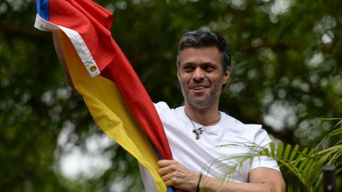 """Venezuelan opposition leader Leopoldo Lopez displaying a Venezuelan national flag, greets supporters gathering outside his house in Caracas, after he was released from prison and placed under house arrest for health reasons, on July 8, 2017.Venezuela's Supreme Court confirmed on its Twitter account it had ordered Lopez to be moved to house arrest, calling it a """"humanitarian measure"""" granted on July 7 by the court's president Maikel Moreno. """"Leopoldo Lopez is at his home in Caracas with (wife) Lilian and his children,"""" Lopez's Spanish lawyer Javier Cremades said in Madrid. """"He is not yet free but under house arrest. He was released at dawn."""" / AFP PHOTO / Federico PARRA [[[AFP]]] VENEZUELA-CRISIS-OPPOSITION-LOPEZ-HOUSE ARREST"""