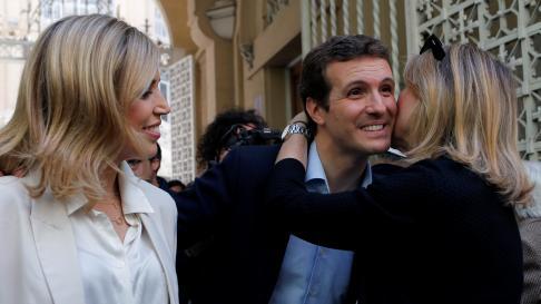 Pablo Casado con su mujer, Isabel Torres, y una votante, después de ejercer su derecho al voto este domingo