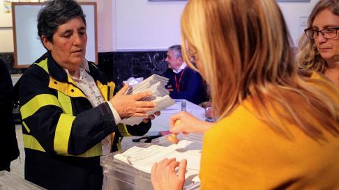 Una trabajadora de Correos entrega en una mesa de Vizcaya los votos emitidos por correo