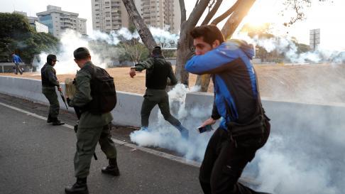 "Military members react to tear gas, near the Generalisimo Francisco de Miranda Airbase ""La Carlota"", in Caracas, Venezuela April 30, 2019. REUTERS/Carlos Garcia Rawlins [[[REUTERS VOCENTO]]] VENEZUELA-POLITICS/"