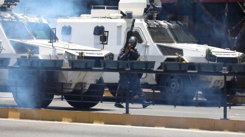 Vista de tanquetas y miembros de la Policía Nacional Bolivariana mientras tratan de bloquear el paso de una manifestación convocada por Guaidó.