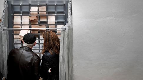 Dos personas eligen sus papeletas para votar en un colegio electoral de España.