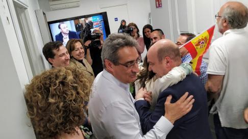 El líder de Vox en Aragón, Santiago Morón, se funde en un abrazo con una militante, al paso del nuevo concejal del partido en Zaragoza, Julio Calvo.