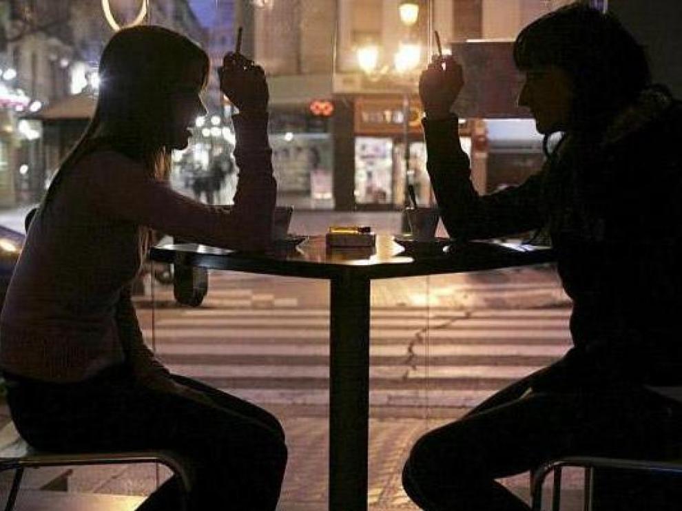 Dos clientes fuman en una cafetería del centro de Zaragoza mientras toman un café