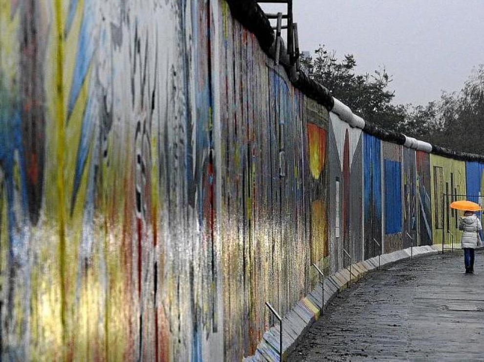 Una mujer pasea junto a un segmento del East Side Gallery de Berlín, el tramo más largo que aún queda en pie del muro.