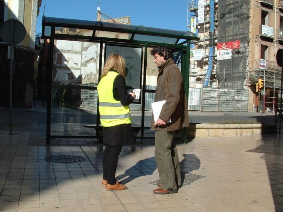 Ana Campos, con chaleco reflectante, realiza una encuesta a uno de los viandantes que pasaba esta mediodía por la confluencia de las calles Coso Bajo y San Lorenzo.