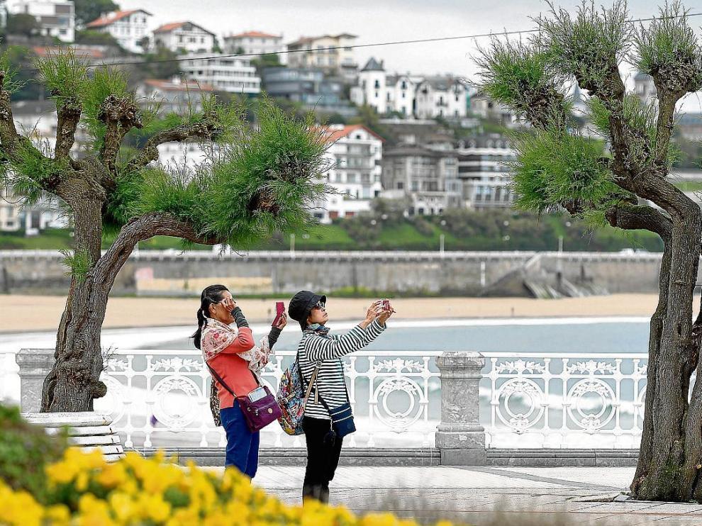 Dos turistas extranjeras toman fotos junto a la playa en San Sebastián.