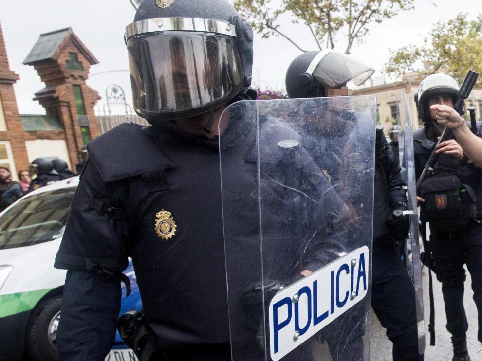 Agentes antidisturbios de la Policía Nacional y de los Mossos d' Esquadra discuten frente al Instituto Can Vilumara de L'Hospitalet de Llobregat. Policía Nacional y Guardia Civil han desplegado a sus agentes en varios colegios electorales de Barcelona par