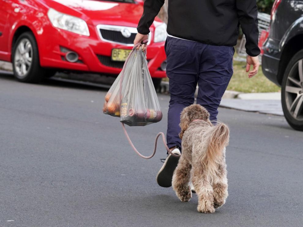 Un hombre lleva la compra realizada en un supermercado en bolsas de plástico de un solo uso que ahora hay que pagar