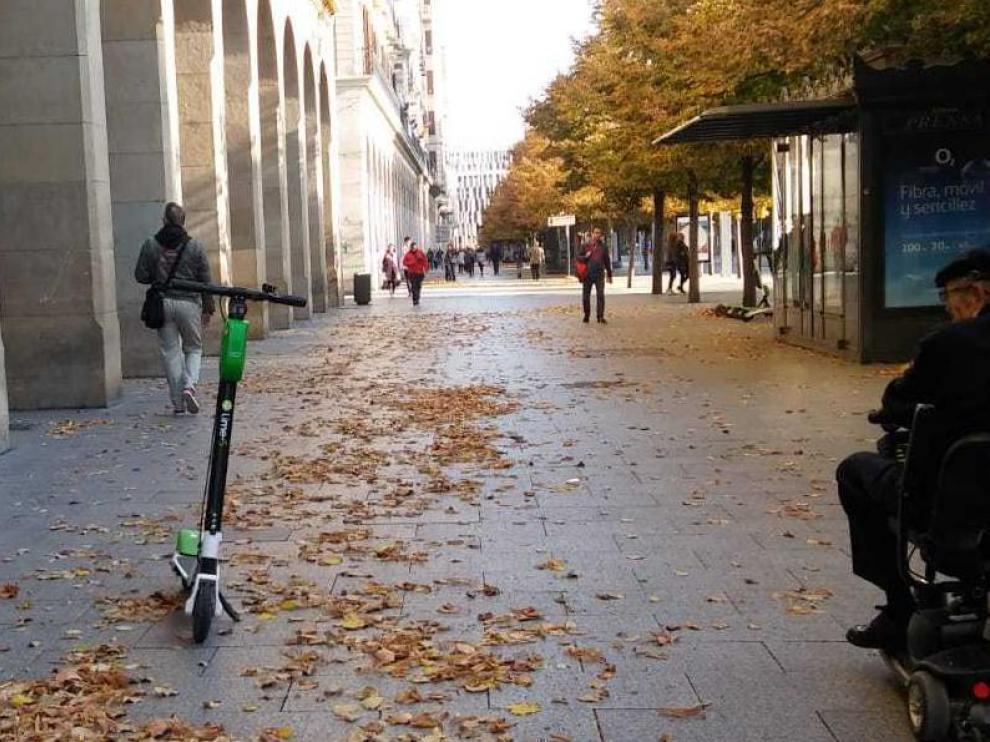 Un hombre en silla de ruedas mira un patinete eléctrico de alquiler abandonado en plena acera, en el paseo de Independencia de Zaragoza este lunes.