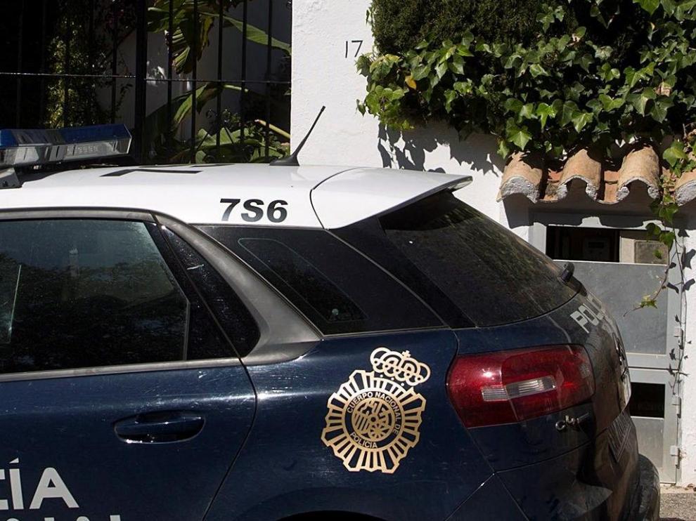 Dos miembros de la Policía Nacional custodian la vivienda donde anoche una mujer de 58 años y de nacionalidad española fue asesinada a puñaladas por su pareja en Estepona (Málaga).