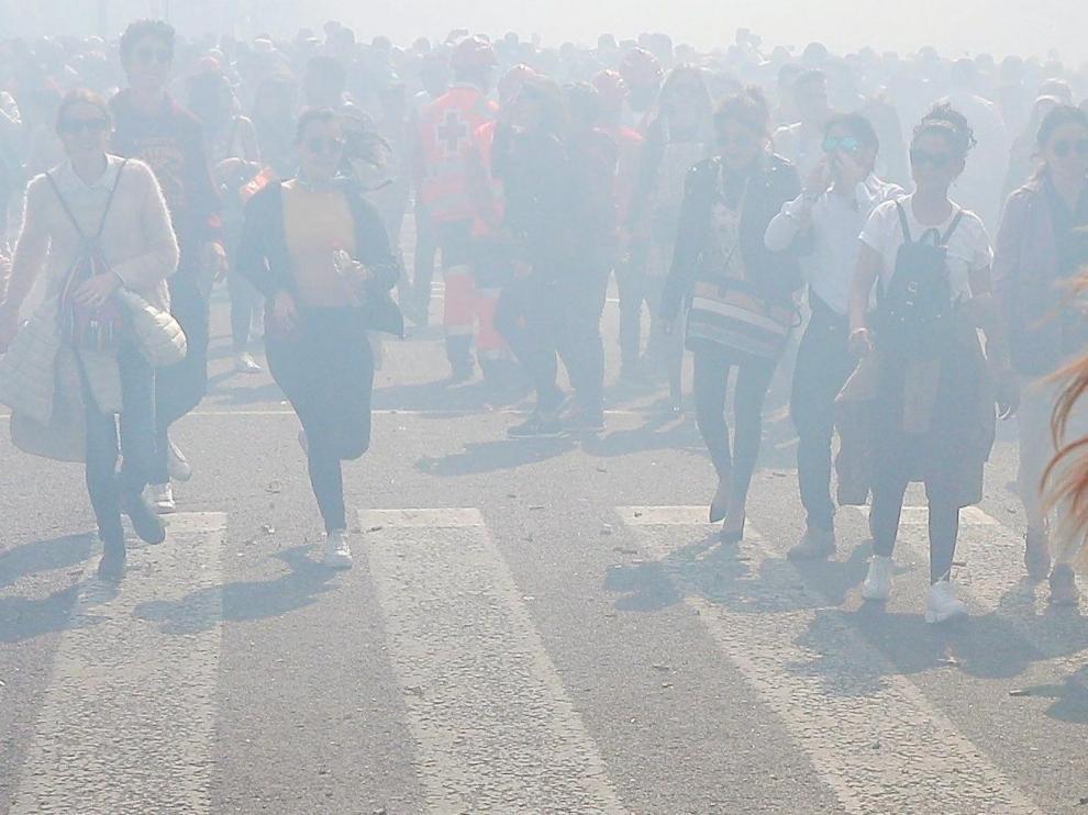 Una aglomeración humana atraviesa la humareda tras el disparo de la última Mascletá oficial de las Fallas en Valencia.