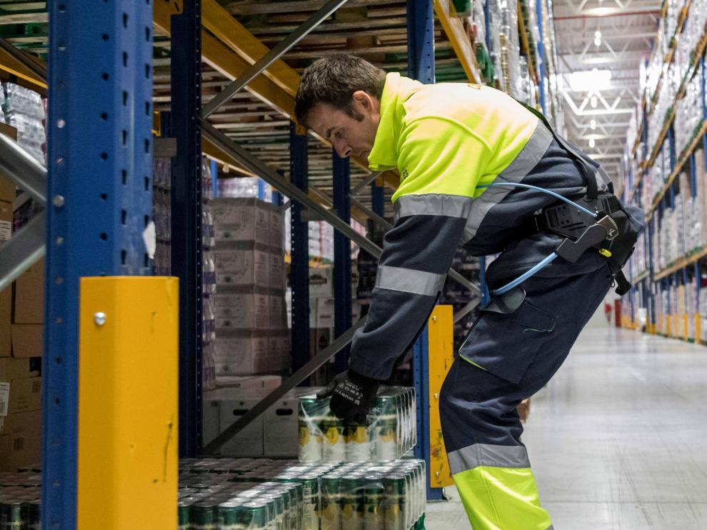 Un trabajador del almacén de Grupo Carreras en Plaza, realiza su labora ayudado con un exoesqueleto.