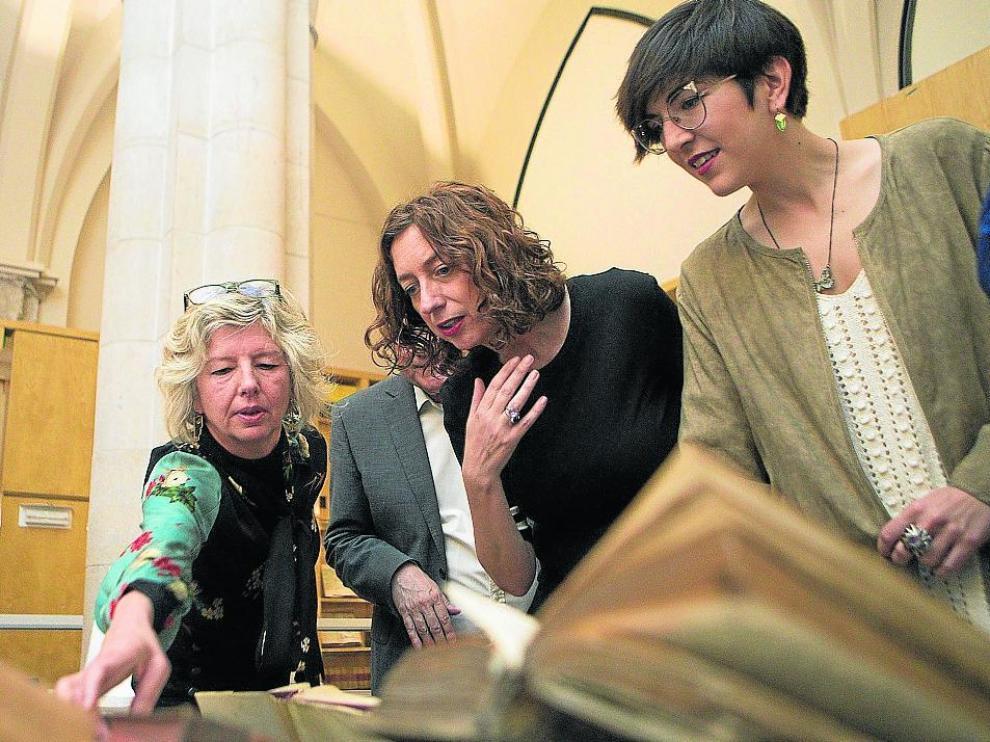 Gascón, con Patricia Luquin y Violeta Barba, ayer, contemplan ejemplares cedidos a las Cortes.