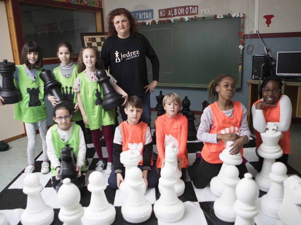 Escolares de primaria del CEIP Zalfonada de Zaragoza, con su maestra Miriam Monreal, tras disputar una partida de ajedrez en el tablero de lona con piezas gigantes