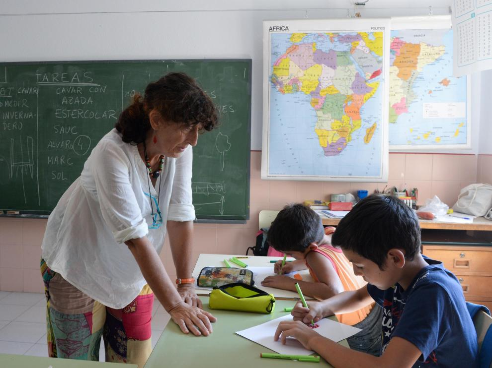 Delfi Ruiz Fernández, maestra de la escuela de Olba, del CRA Javalambre (Teruel), observa el trabajo de dos de sus alumnos