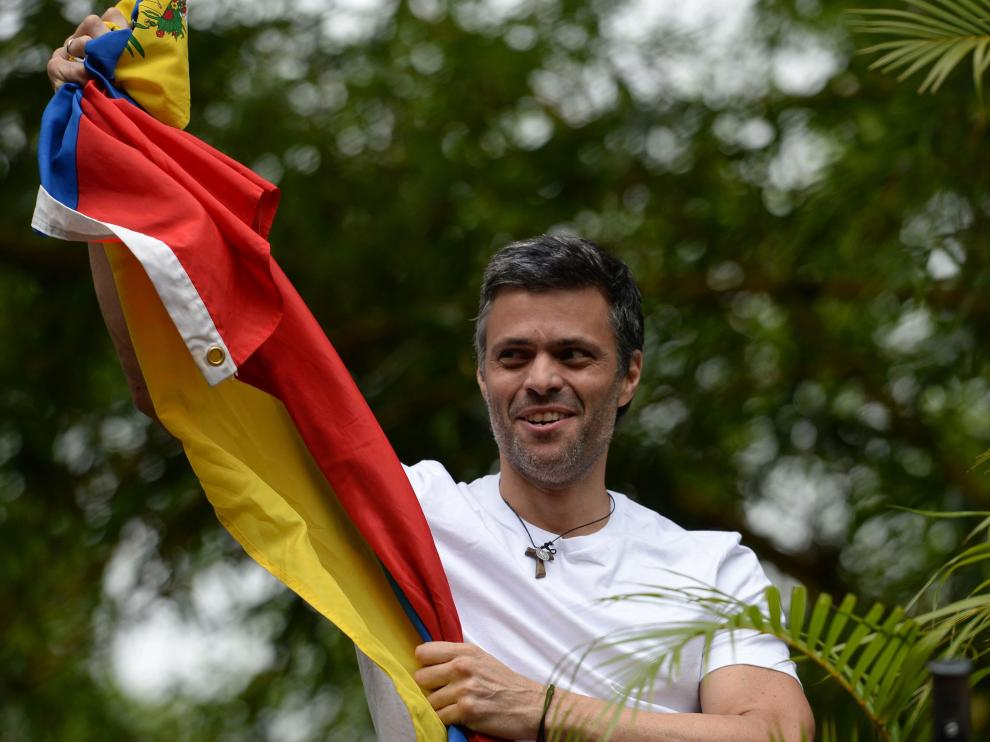 "Venezuelan opposition leader Leopoldo Lopez displaying a Venezuelan national flag, greets supporters gathering outside his house in Caracas, after he was released from prison and placed under house arrest for health reasons, on July 8, 2017.Venezuela's Supreme Court confirmed on its Twitter account it had ordered Lopez to be moved to house arrest, calling it a ""humanitarian measure"" granted on July 7 by the court's president Maikel Moreno. ""Leopoldo Lopez is at his home in Caracas with (wife) Lilian and his children,"" Lopez's Spanish lawyer Javier Cremades said in Madrid. ""He is not yet free but under house arrest. He was released at dawn."" / AFP PHOTO / Federico PARRA [[[AFP]]] VENEZUELA-CRISIS-OPPOSITION-LOPEZ-HOUSE ARREST"