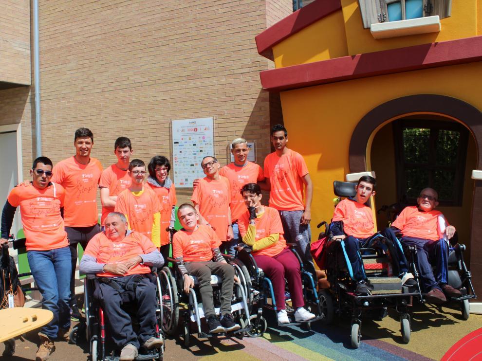 Los jugadores Damián Musto y Chimy Ávila y los usuarios de Aspace posan con la camiseta de la marcha de este año.