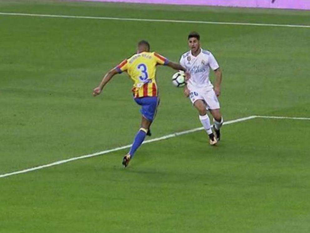 Mano involuntaria de Vezo, defensor del Valencia, en el Bernabéu. Este año no fue considerada penalti. A partir del 1 de julio, lo será.