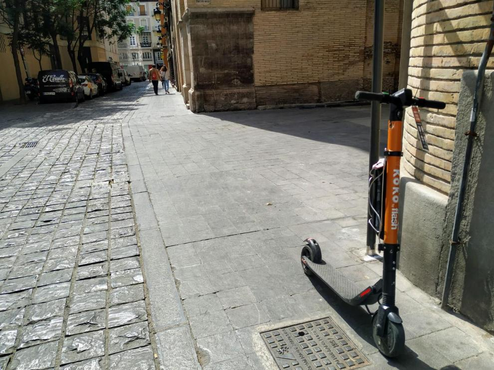 El patín, con el boletín de denuncia, en la acera de la calle de Agustines, junto a la Audiencia de Zaragoza.
