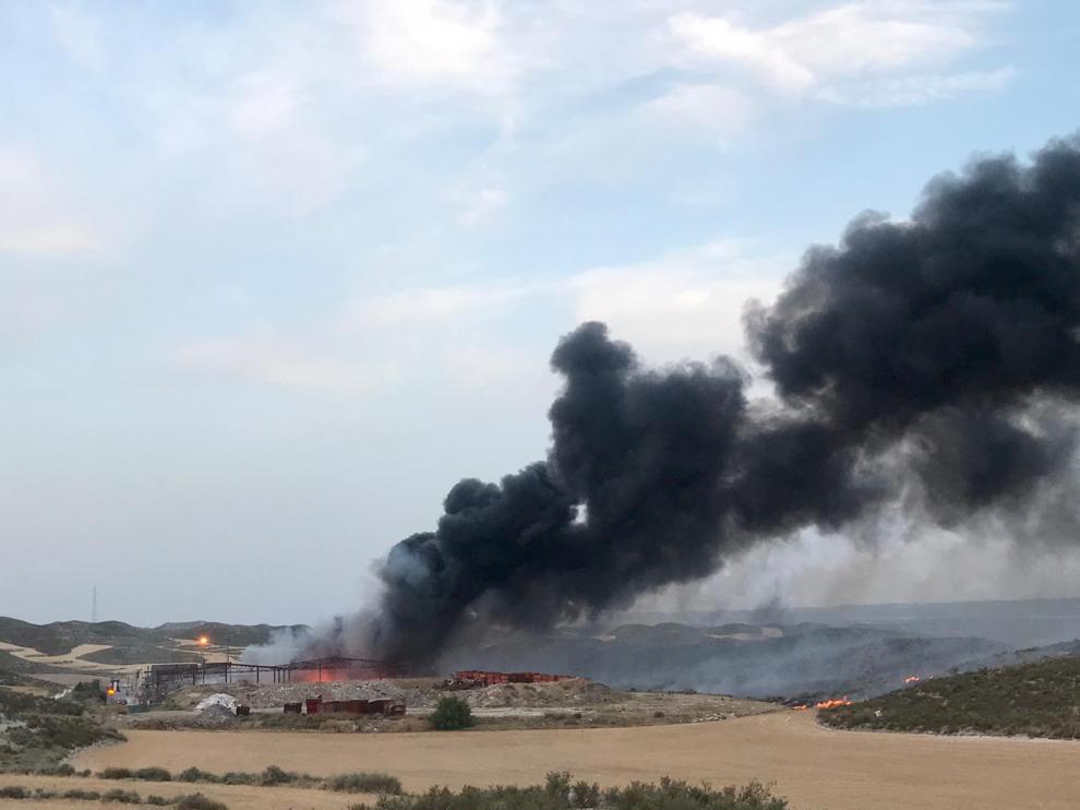 Los bomberos tratan de impedir que las llamas se extiendan por los cultivos que rodean la planta.