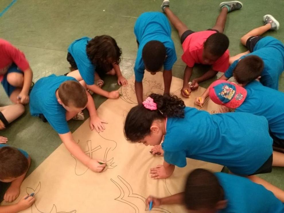 Algunos niños hacen un mural en las colonias urbanas de Cruz Roja