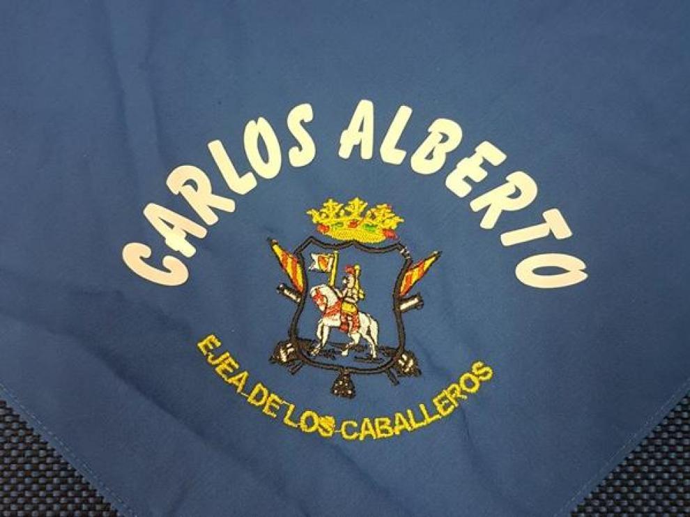 El pañuelo es azul y lleva bordado el escudo y el nombre del niño o niña.