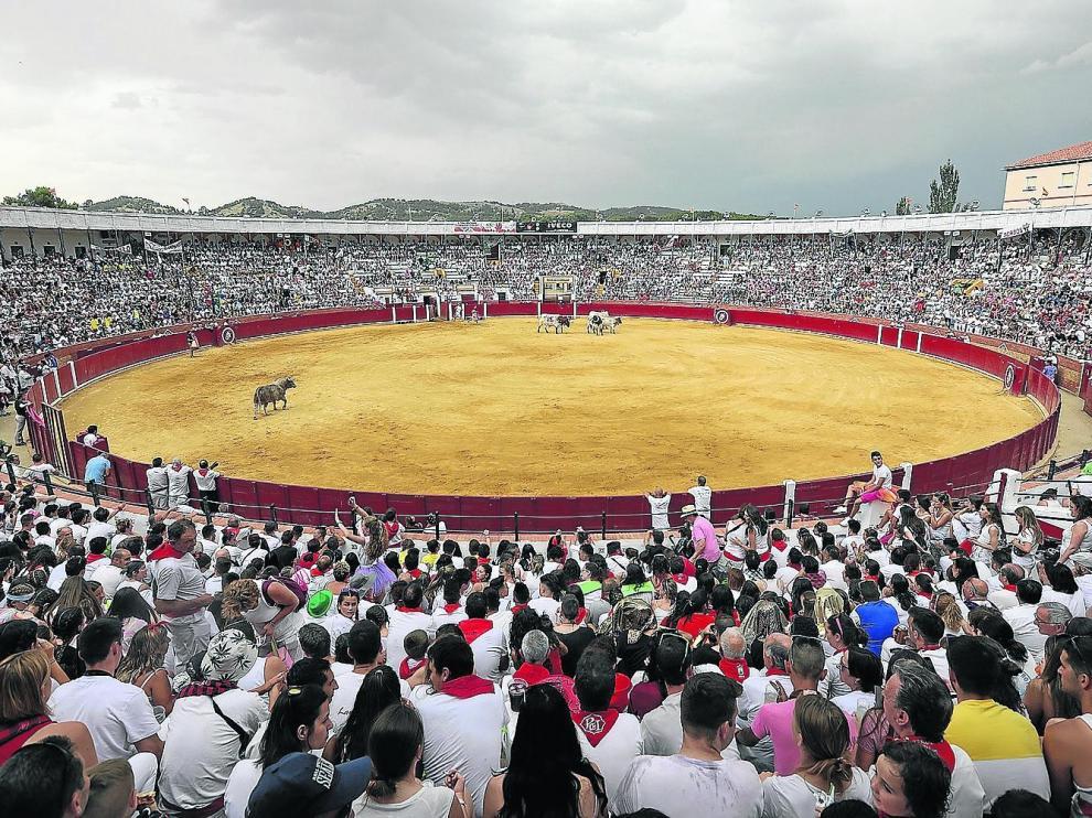 Una plaza de toros a rebosar de peñistas y jóvenes disfrazados, durante la tradicional merienda del domingo de La Vaquilla.