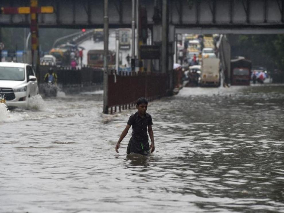 Un joven huye de la corriente de agua provocada por las lluvias.