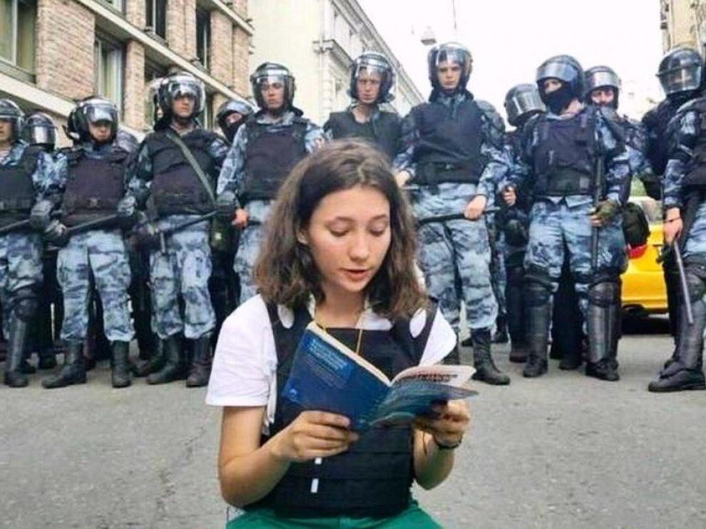 La joven Olga Misik leyendo la constitución frente a la policía.