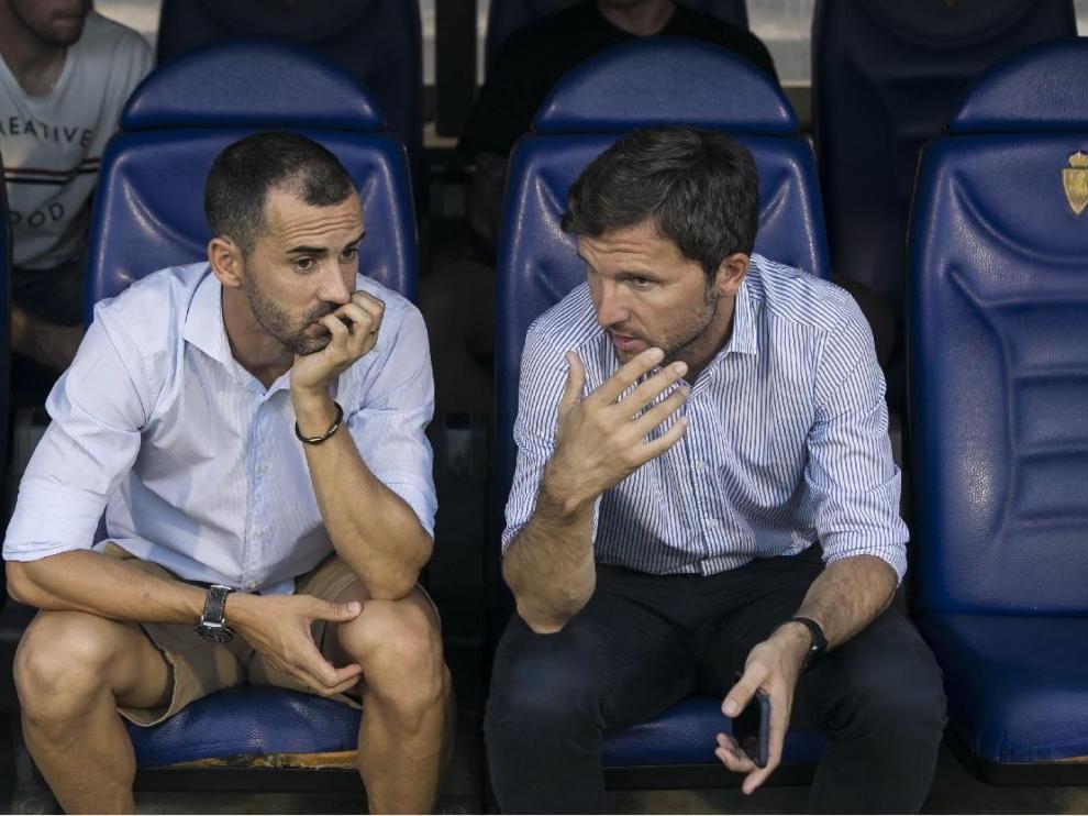 Miguel Linares y Lalo Arantegui, el sábado una hora antes del Real Zaragoza-Tenerife del debut liguero, charlan en el banquillo de La Romareda. El delantero aragonés no estaba convocado por Víctor Fernández.
