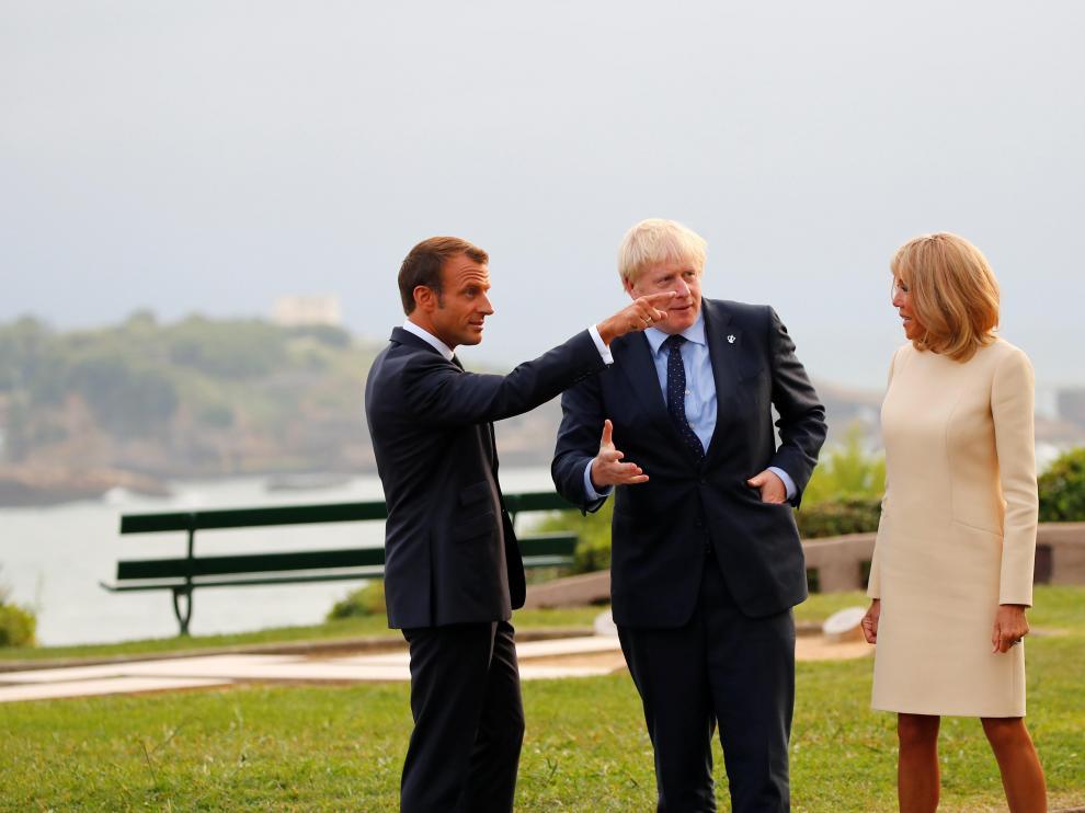 El presidente francés y su mujer conversan con el primer ministro británico.