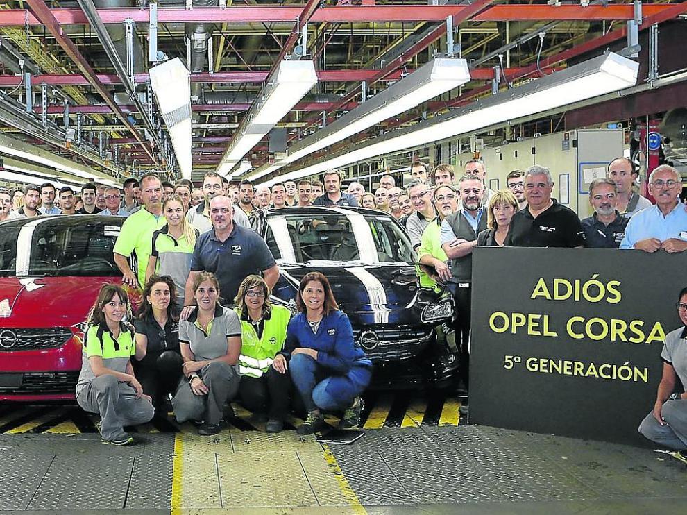 Trabajadores de la planta de Opel España, del grupo PSA, posan con unidades de la quinta y de la sexta generación del Corsa, ayer