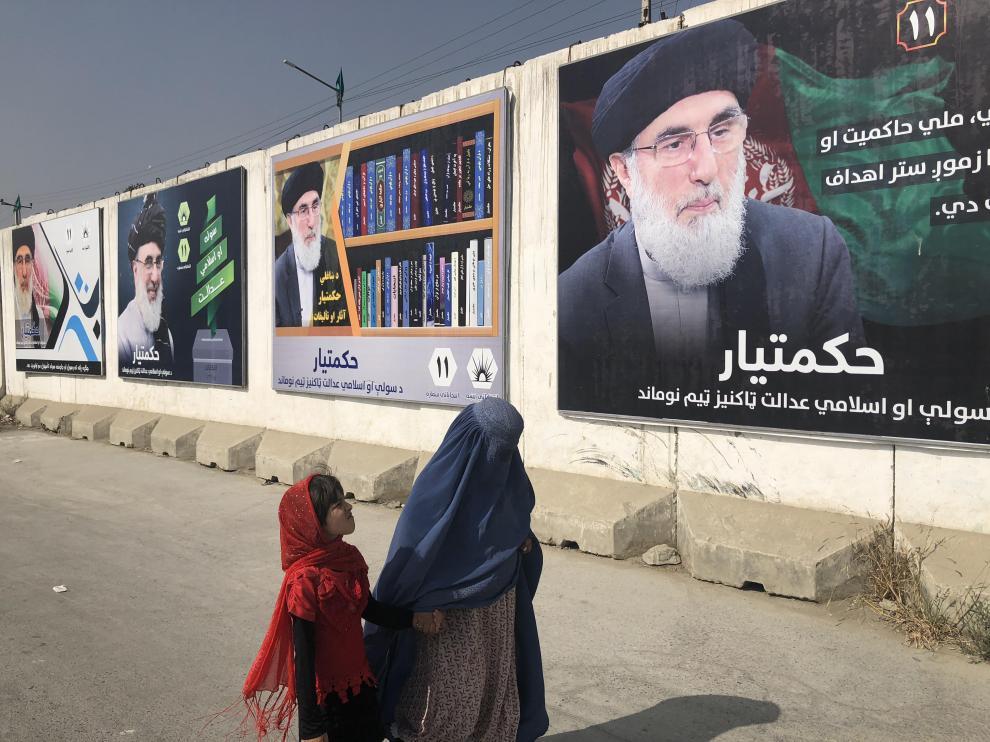 Una mujer con burka y una niña pasan por un muro con publicidad electoral del señor de la guerra Gulbudin Hekmatyar