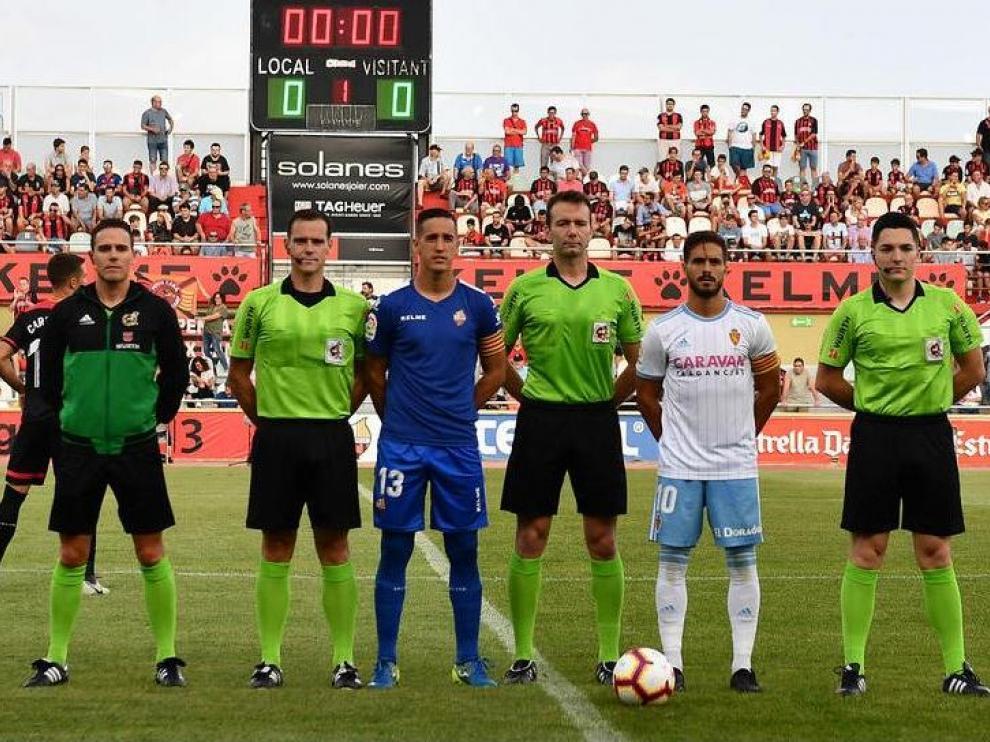 El árbitro López Toca, cántabro, en el centro de la imagen antes del Reus-Real Zaragoza del año pasado, el segundo y último partido que ha dirigido a los zaragocistas desde su aparición en Segunda División hace tres campañas.Badía, portero del Reus, y Javi Ros, del Zaragoza, posan a su lado junto con el resto del equipo arbitral.
