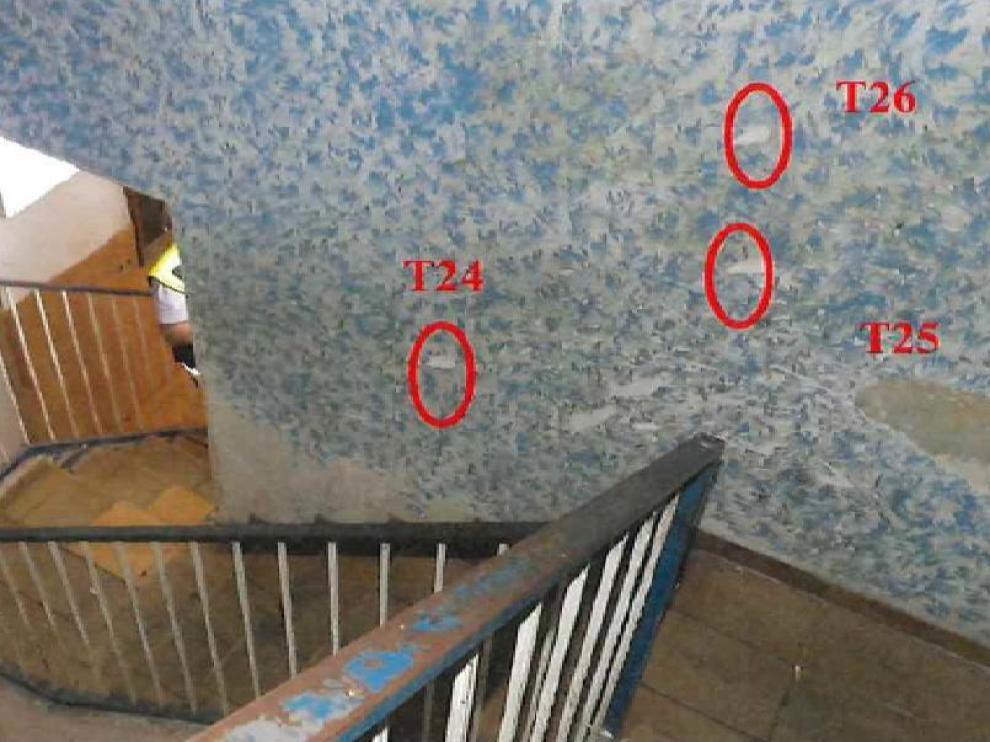Marcados en la pared de la escalera, tres de los once disparos que efectuaron los policías en el portal del número 76 de la calle Pignatelli de Zaragoza.