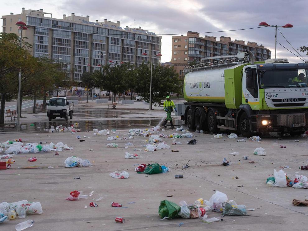 Operarios de FCC limpian a primera hora la enorme cantidad de basura que se acumula en el botellón de Valdespartera