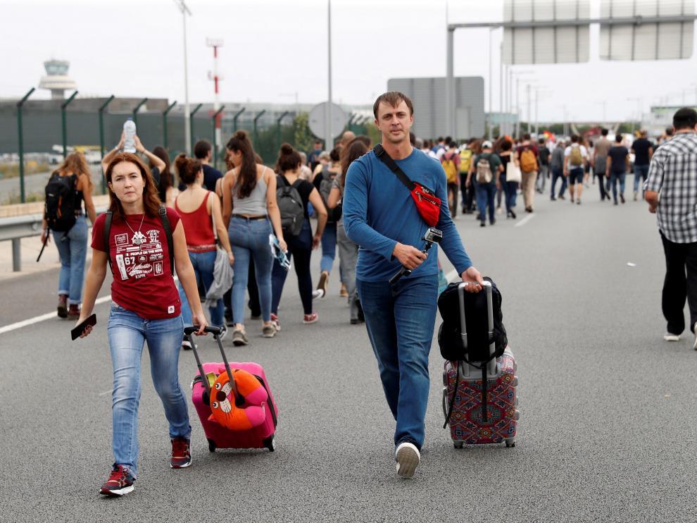 Dos pasajeros llegan caminando al aeropuerto del Prat.