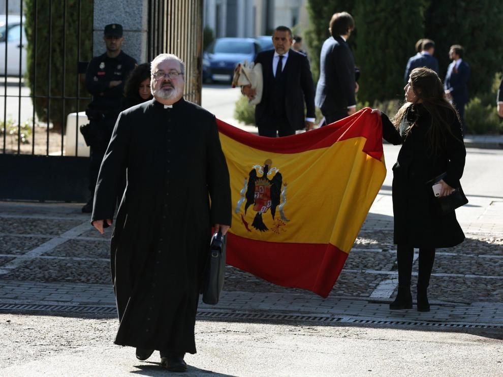 El sacerdote Ramón Tejero, que ha oficiado la misa de la reinhumación de Francisco Franco, a su salida del cementerio de Mingorrubio junto a dos familiares del dictador que portan una bandera española con el escudo franquista.