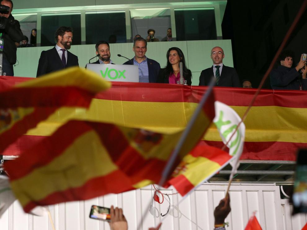 El equipo de Vox saluda a sus simpatizantes en el exterior de la sede de Madrid durante el seguimiento de la noche electoral.