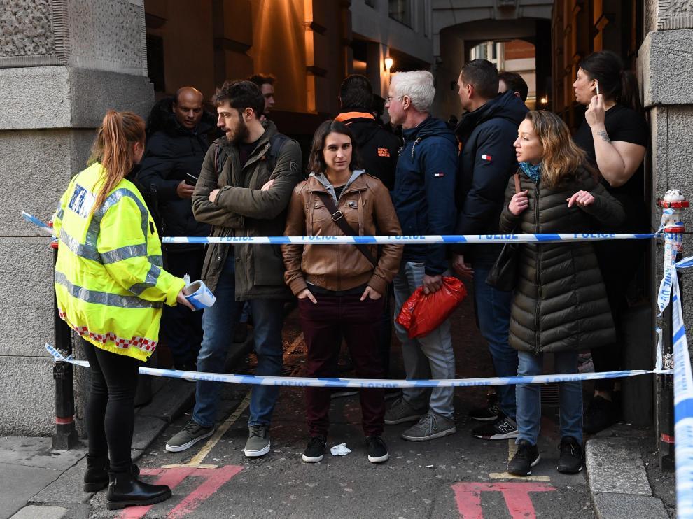 Una policía junto a varias personas en el puente de Londres.