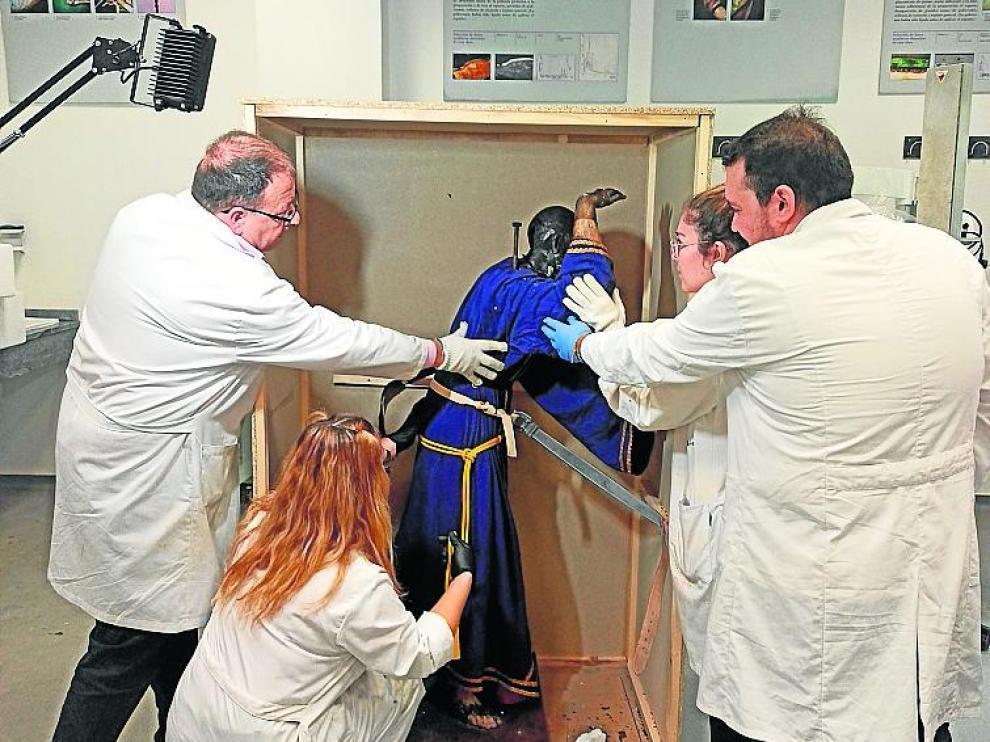 Personal de la facultad de Sevilla desembala el Cristo.
