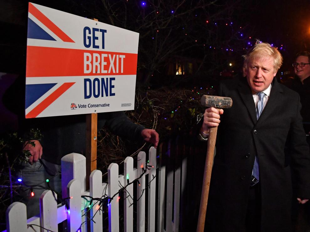 """Britain's Prime Minister and Conservative party leader Boris Johnson poses with a sledgehammer, after hammering a """"Get Brexit Done"""" sign into the garden of a supporter, in South Benfleet, Britain December 11, 2019. Ben Stansall/Pool via REUTERS [[[REUTERS VOCENTO]]] BRITAIN-ELECTION/JOHNSON"""