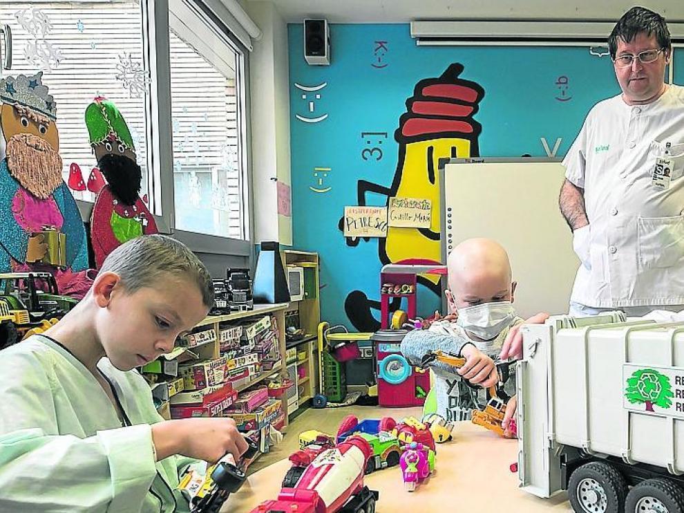 Adam y Mario juegan con una variada colección de coches en el aula educativa