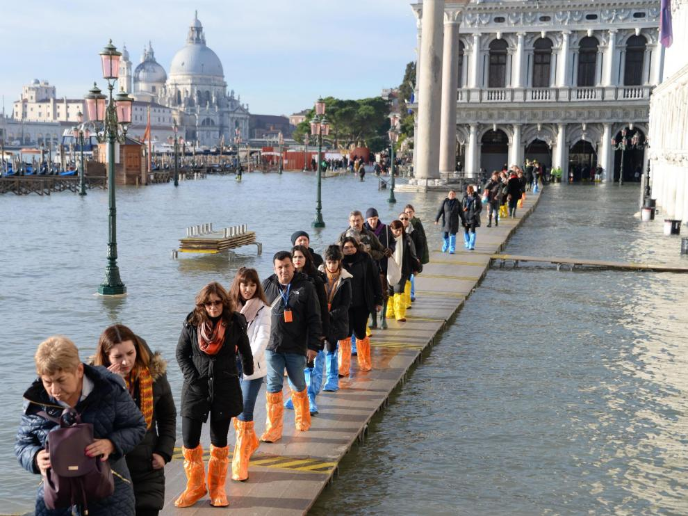 Venice (Italy), 23/12/2019.- A group of tourists walks in single file along a walkway, on the San Marco pier flooded by high tide, Venice, Italy, 23 December 2019. The high tide reached 144 cm. (Italia, Niza, Venecia) EFE/EPA/Andrea Merola High waters in Venice