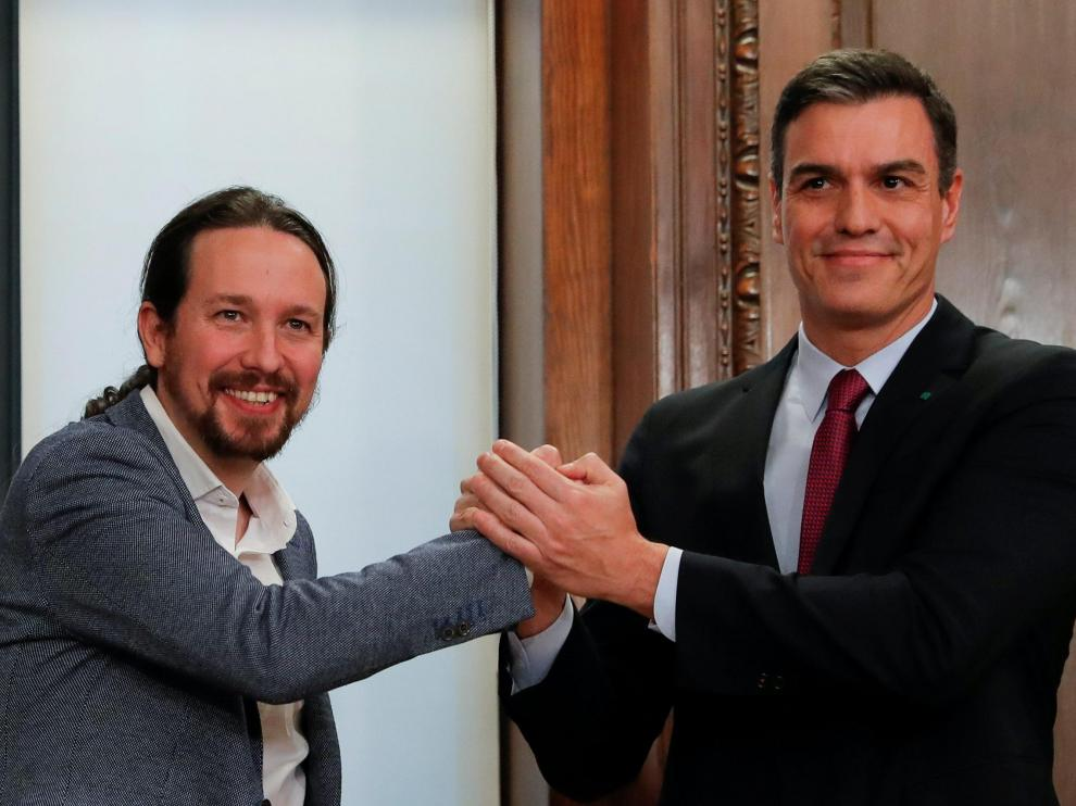 Spain's acting Prime Minister Pedro Sanchez and Unidas Podemos (Together We Can) leader Pablo Iglesias shake hands as they present their coalition agreement at Spain's Parliament in Madrid, Spain, December 30, 2019. REUTERS/Susana Vera [[[REUTERS VOCENTO]]] SPAIN-POLITICS/