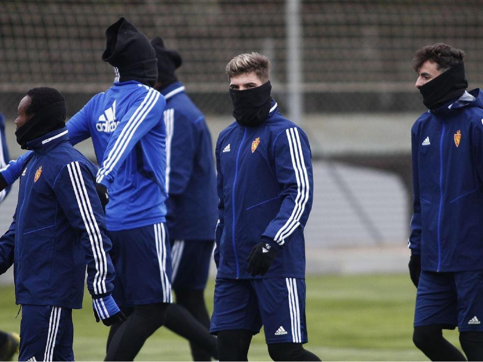 Igbekeme, Guti y Francés, acompañados por otros 'anónimos' compañeros protegidos del intenso frío en el entrenamiento matinal del Real Zaragoza en la Ciudad Deportiva.